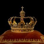 The picture shows a gold crown next to a black backdrop.