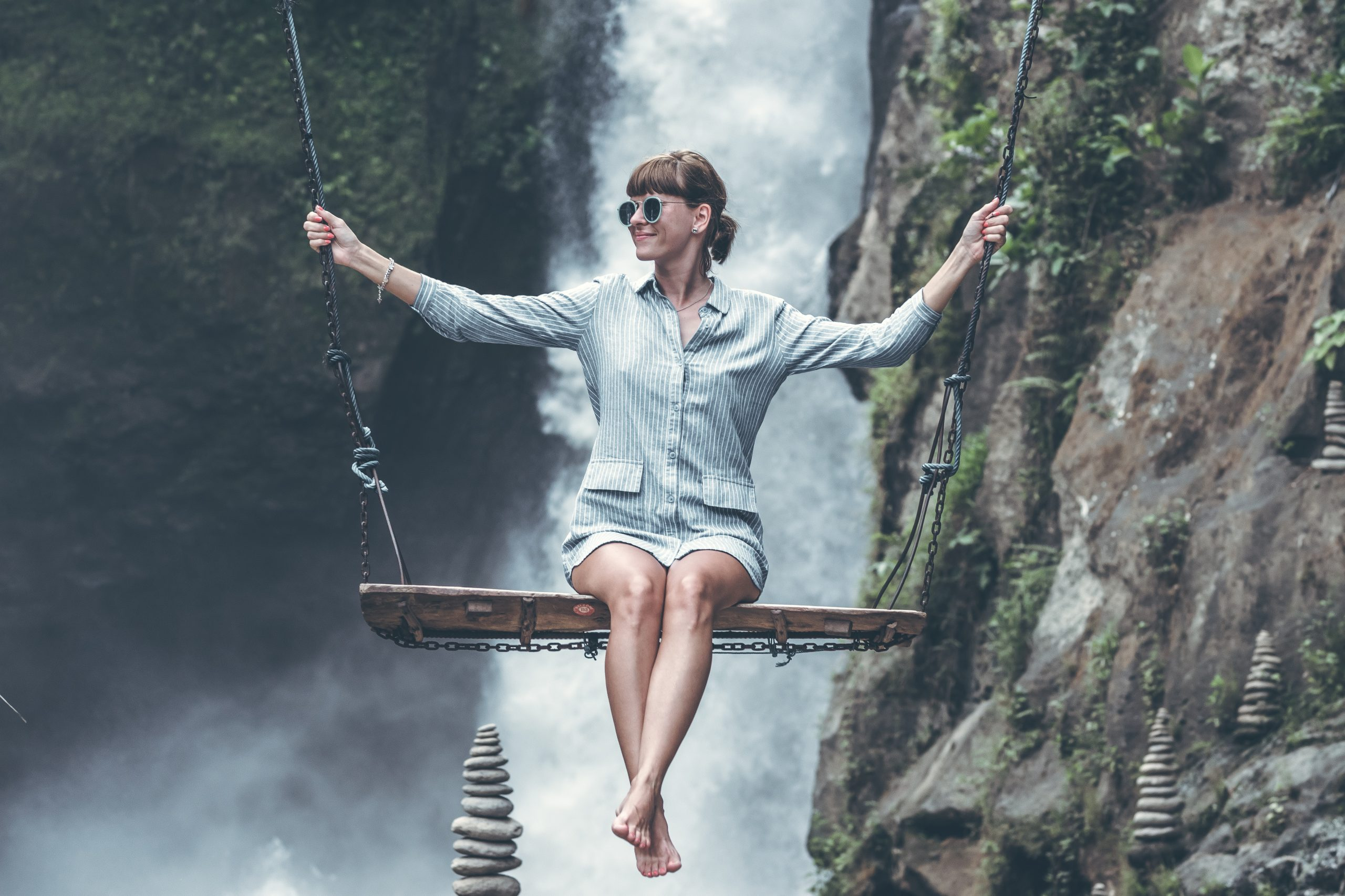 A woman balancing on a wooden swing.